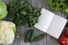 Note book and composition of vegetables on grey wooden desk. Royalty Free Stock Photos