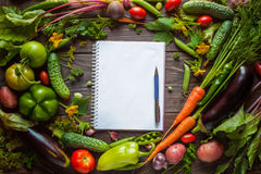 Note book and composition of vegetables on wooden desk Stock Photography
