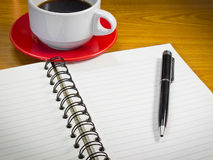 Note book and cup of coffee. Note book and pen with a cup of coffee Royalty Free Stock Photo