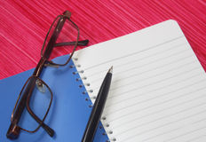Note book with eye glasses and pen. On pink background royalty free stock photo