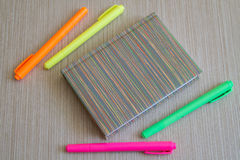 Note book and four colored Markers. Office Supplies. Notebook and four colored Markers at the Wooden Background Stock Image