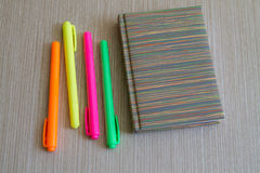Note book and four colored Markers. Office Supplies. Notebook and four colored Markers at the Wooden Background Stock Images