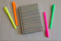 Note book and four colored Markers. Office Supplies. Notebook and four colored Markers at the Wooden Background Stock Photography