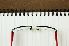 Note book with glasses. On hard compressed paper board Royalty Free Stock Photo