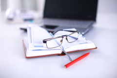 A note book, laptop, pen, graph paper document on the office desk table behind white blind.  Stock Photo