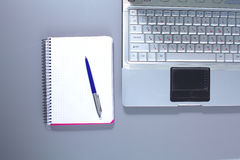 A note book, laptop, pen, graph paper document on the office desk table behind white blind.  Royalty Free Stock Image