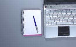 A note book, laptop, pen, graph paper document on the office desk table behind white blind.  Royalty Free Stock Photos