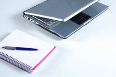 A note book, laptop, pen, graph paper document on the office desk table behind white blind.  Stock Images