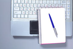 A note book, laptop, pen, graph paper document on the office desk table behind white blind.  Royalty Free Stock Photography