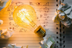 Note book and light bulb with drawing graph Stock Photography