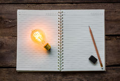 Note book and light bulb Royalty Free Stock Image