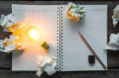 Note book and light bulb Stock Image