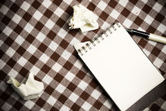 Note book paper on old wooden background ; still life. Royalty Free Stock Photo