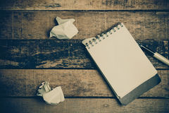 Note book paper on old wooden background ; still life. Royalty Free Stock Photos