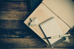 Note book paper on old wooden background ; still life. Stock Photos