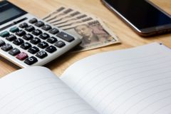 Note book with pen,calculator, smart phone, japnese yen banknote. Background Stock Photography