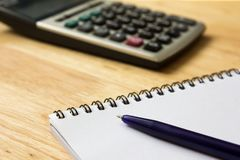 Note book with pen and calculator on wood table. Note book with pen and calculator on wooden table background Stock Photography