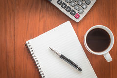 Note book with pen and a cup of coffee on wood table. Royalty Free Stock Image