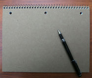 Note book and pen on desk. Of wood Royalty Free Stock Images
