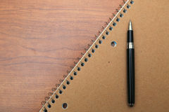 Note book and pen on desk. Of wood Stock Photography