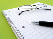 Note book with pen and glasses Royalty Free Stock Photos