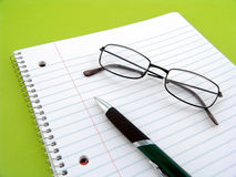 Note book with pen and glasses Royalty Free Stock Images