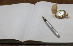 Note Book and Pen with gold watch. A view of a silver pen on a note book with a gold pen Royalty Free Stock Image