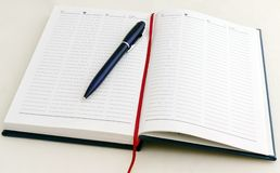 Note-book with pen. Writingpad (note-book) with date and one dark ball-point pen royalty free stock images