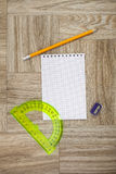 Note book, pencil and protractor ruler on a wooden texture Stock Image