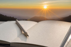 Note book and pencil during sunrise Stock Image