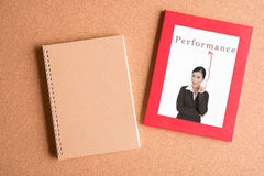 Note book and  photo of business woman in frame on wooden table Stock Photo