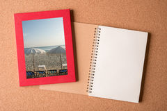 Note book and picture of beach in the frame on wooden table Stock Photos