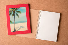 Note book and picture of beach in the frame on wooden table Stock Photo