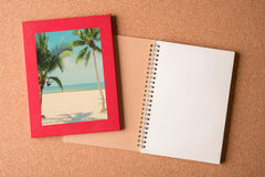 Note book and picture of beach in the frame on wooden table Royalty Free Stock Photos