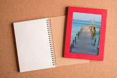 Note book and picture of old ship dock in frame on wooden table Royalty Free Stock Photos