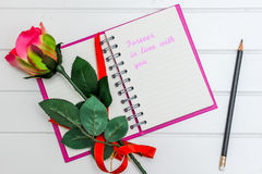 Note book. That says Forever in love with you And there is a red rose Stock Image