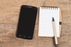 Note book  and smart phone on wood Stock Images