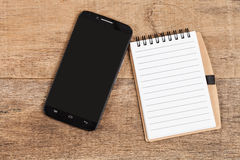 Note book  and smart phone on wood Royalty Free Stock Photography