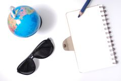 Note book from top view. White office desk table with open note book, color pencil globe, and sun glasses . Top view with copy space, flat lay Stock Images