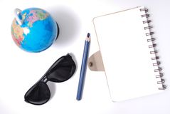 Note book from top view. White office desk table with open note book, color pencil globe, and sun glasses . Top view with copy space, flat lay Stock Photography