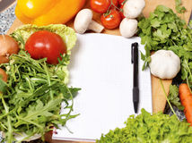 Note book among the vegetables Stock Photos