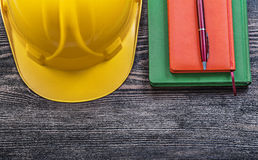 Note-books ball-point pen building helmet on wooden board constr Royalty Free Stock Image