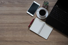 Note books, pens, coffee, mobile phones and laptop are placed on table wooden Royalty Free Stock Images