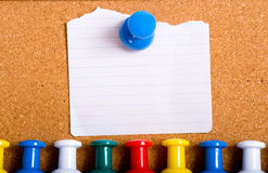 Note on Bulletin Board. A torn white note stuck to a bulletin board with an oversized push pin, with a row of push-pins or tacks below.  with copy space Royalty Free Stock Photos