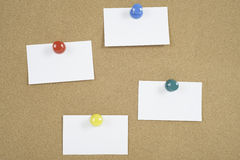 Note Card Bulletin Board. Four note cards on a bulleting board held by four colorful push pins royalty free stock photo