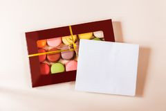 Note card and different colorful macaroons in gift box. On beige background Stock Image