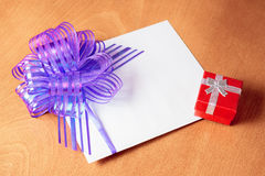 Note card with violet bow and red gift box Stock Photography