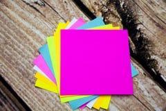 Note collante d'autocollants de papier multicolores sur le fond en bois Formules en blanc pour le texte Photos stock