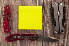 Note collante jaune avec l'espace vide pour un texte sur le fond en bois Panne émotive de chasse ou de santé avec des couteaux photographie stock
