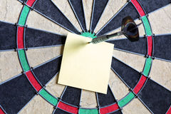 Note collante jaune sur le dartboard Photos stock